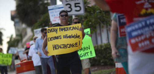 "man standing in a protest line holding a sign that reads ""Every American Deserves Affordable Healthcare!"""